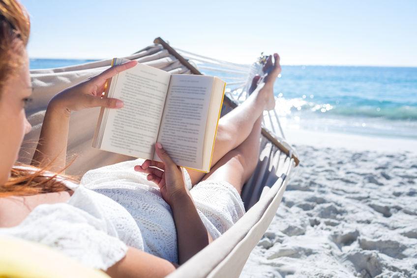 woman lying by ocean, reading book